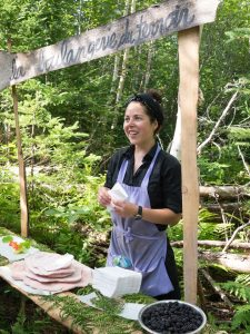 The artist Amelie Brindamour stands behind a bakery counter set up in the forest as part of her 2016 project, La Boulangerie du Terroir.