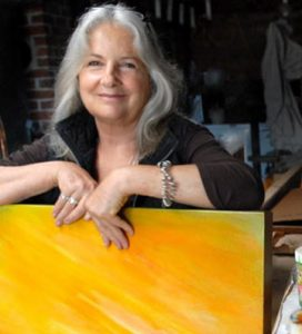 Photo of Canadian artist Roberta Pyx Sutherland, sitting with a yellow-painted canvas propped up in her lap. She is looking at the camera and smiling. To the right, there is a table with paintbrushes and cups of paint.